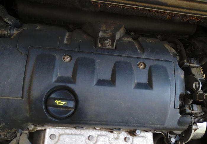 Для замены свечей зажигания на Пежо 308 надо демонтировать пластиковую накладку двигателя