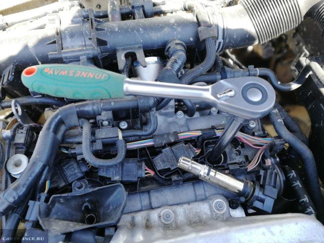 Откручивание свечи зажигания ключом с трещоткой на двигателе Фольксваген Тигуан